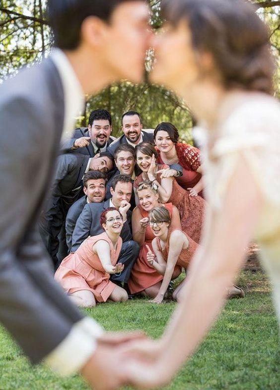 sposi che si baciano con invitati